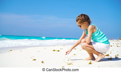 Adorable little girl at beach during summer vacation drawing...