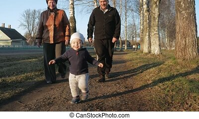 An attractive kid runs away from his grandparents in the park to his mother. A woman takes it and whirls in the rays of the setting sun