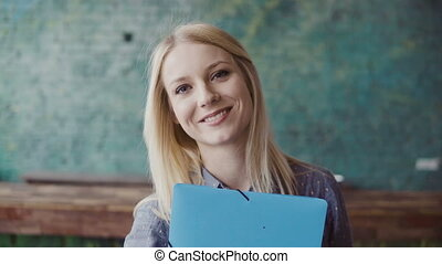 Portrait of young caucasian blonde woman looking at camera...