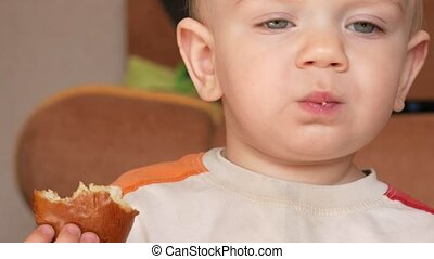 Cute kid two years of eating a muffin at home. Close-up.