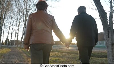 Loving elderly couple walking in the park at sunset. Nearby there is a road. A woman in a brown leather jacket. The man is dressed in a black sweater.