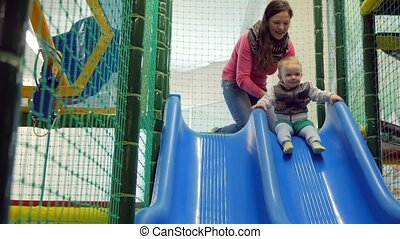A cute kid pulls off the blue roller coaster in an amusement...