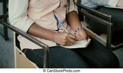 Close-up view of african female hands. Woman sitting on a...