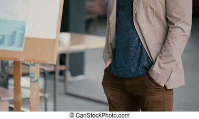 Close-up view of male standing in light loft office and...
