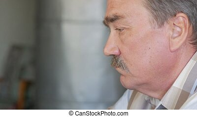 An elderly man with a mustache sits behind a laptop and solves problems. He looks seriously at the monitor