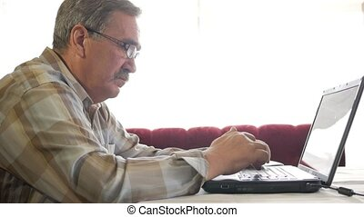 Senior man in glasses works for a laptop. He looks seriously at the monitor
