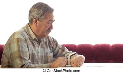 A man of age uses smartwatches at home. He watches messages and dictates what to find on the Internet