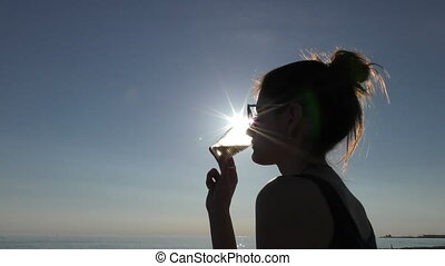 Young attractive woman on the beach at sunset drinking from glass