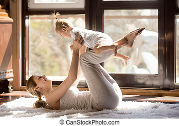 Young attractive yogi mother and baby daughter exercising at...