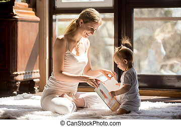 Young attractive mother and baby sitting reading a book together