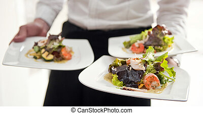 Waiter, carrying three plates with a rich salad