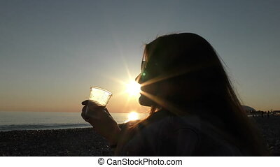 Young attractive woman on the beach at sunset time in...
