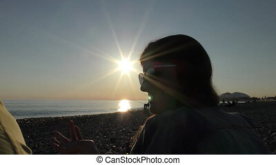 Young attractive woman on the beach at sunset time talking...