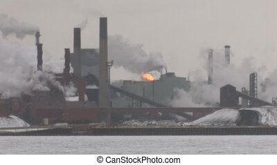 Steelmill. - Shot taken across frozen lake of busy, grey...