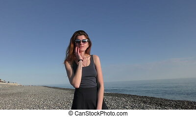 Young attractive woman in sunglasses on the pebble beach...