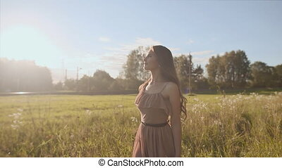 Beautiful girl with long hair goes through the meadow among the flowers. The girl in the rays of the sun.