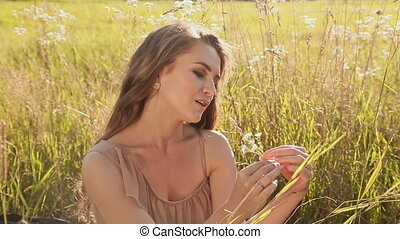 Young beautiful girl sitting on a green meadow. She sings the song holding flowers. Closeup.