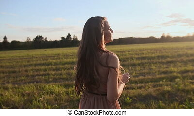 The girl goes on a footpath in a field and singing a song. Girl spinning in the rays of the sun.