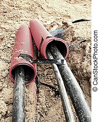 Excavation of trench with black cables in protective HDPE...