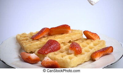 Adding cream to waffles with strawberries, slow motion