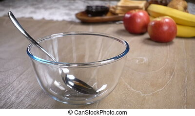 corn flakes are poured into a glass bowl with milk, slow...