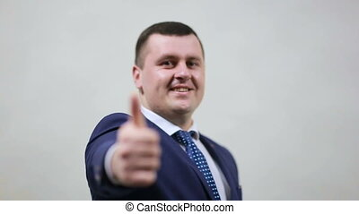 Young happy businessman shows thumb up on white background in studio. Caucasian man thumbs up posing and smiling at camera, right hand rack focus