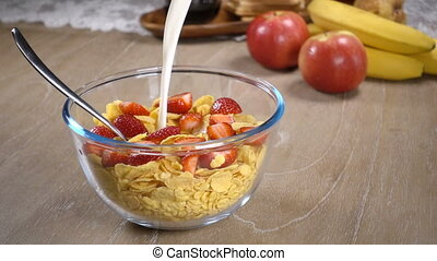 Milk is poured into a bowl of cornflakes and strawberries
