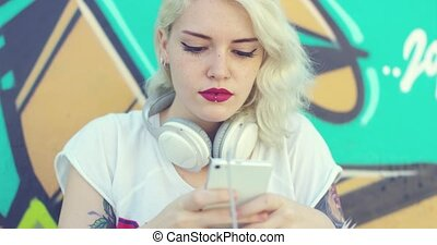 Hipster woman browsing her mobile for music - Hipster...