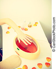 Woman getting paraffin hand treatment at beautician -...
