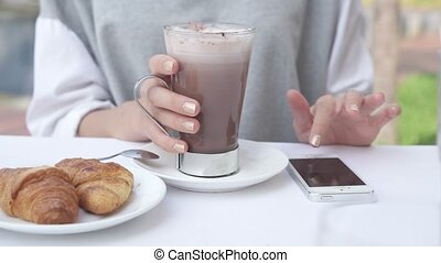 Young woman write message on smartphone while drinking cacao...