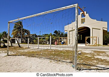 Soccer net surrounded by debris - A worn out soccer net in a...