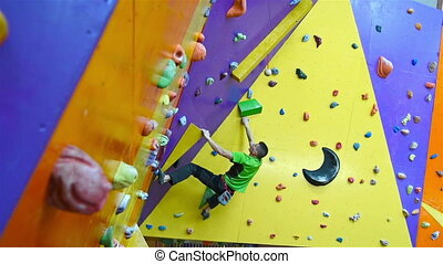 Athletic Climber Man Climbing On Practice Wall Indoors. View...