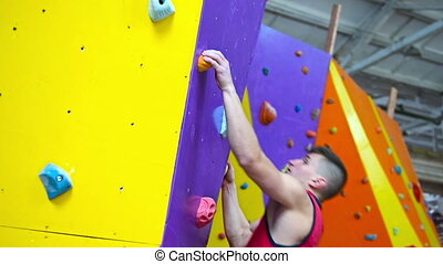 Muscular Climber Man Climbing Up On Color Rock Wall In Gym