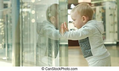 A cute blond boy of two years is considering a store through...