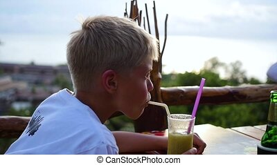 a young man in a cafe drinking a cocktail on terrace. outdoors
