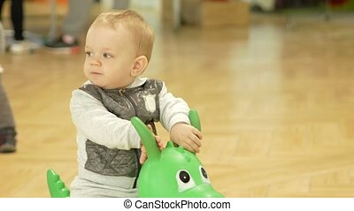 Cute blond boy two years old jumping on an inflatable horse...