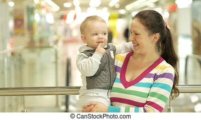 Mom keeps a pretty blond son in his arms in the mall....
