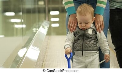 A cute blond boy of two years with his mother climbs the escalator in a large shopping center. The kid looks all around