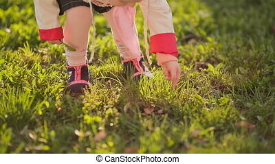 Little russian girl in pink headscarf walking at sunset in a meadow.