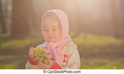 A little Russian girl in a pink headscarf eat grapes at...