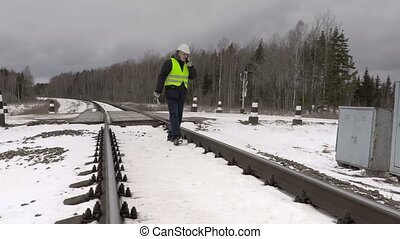 Railroad worker talking on phone near electrical enclosures