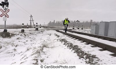 Railroad worker with warning sign talking on phone and...