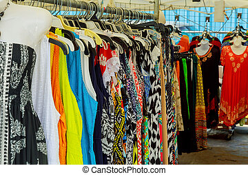Colorful ladies clothes on clothes hangers at a market. -...