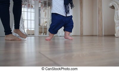 Mother and little boy walking on wood floor at home