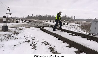 Railroad worker with warning sign on railway
