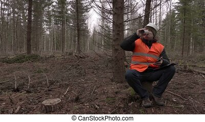 Lumberjack sitting and drinking coffee in forest