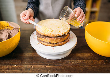 Woman cook hands pours cake with sugar syrup. Tasty dessert...