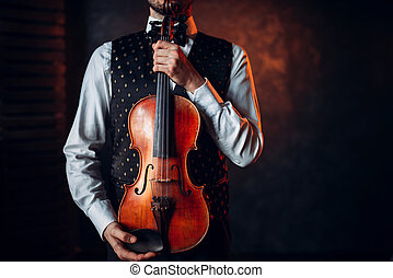 Portrait of male person holding wooden violin. Fiddler with...