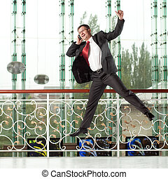 smiling jumping man with mobile phone on background of glass...