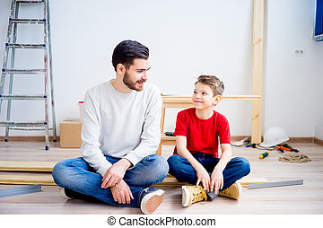 Father and son hammering nails - A portrait of father...